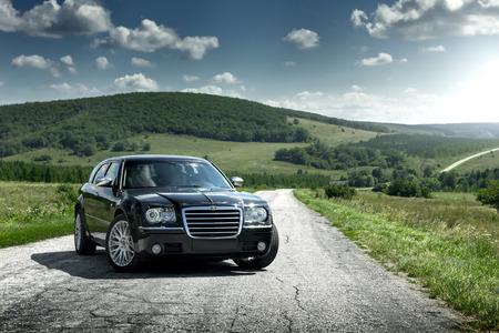 chrysler: Saratov, Russia - August 9, 2015: Black car Chrysler 300c standing on the asphalt road at daytime