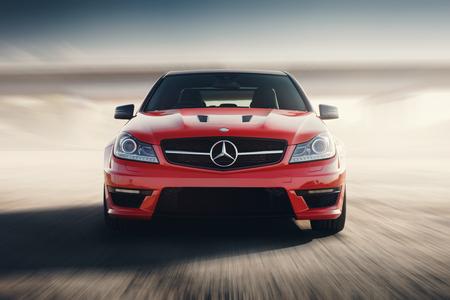 Saratov, Rusia - 24 de agosto de 2014: Rojo del coche deportivo Mercedes-Benz C63 AMG Drive de velocidad en la carretera de asfalto en la puesta