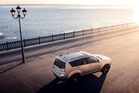 outlander: Saratov, Russia - November 27, 2014: Car Mitsubishi Outlander stay on embankment in city near river and lantern at sunset