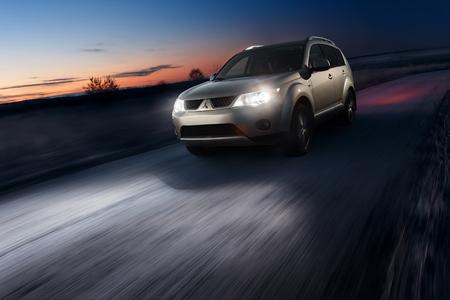 xenon: Saratov, Russia - November 27, 2014: Car Mitsubishi Outlander fast drive on asphalt road at dusk