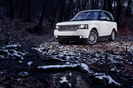Saratov, Russia - December 11, 2014: White premium car Land Rover Range Rover stay in forest at twilight