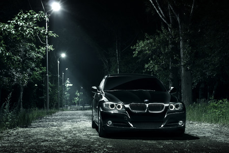 Saratov, Russia - June 12, 2015: Black car BMW E90 stay in darkness forest at night Editorial