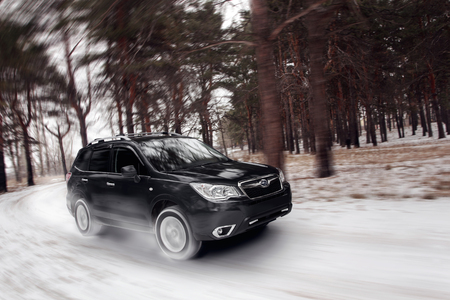 forester: Saratov, Russia - January 01, 2014: Black car Subaru Forester speed drive on off road at winter daytime