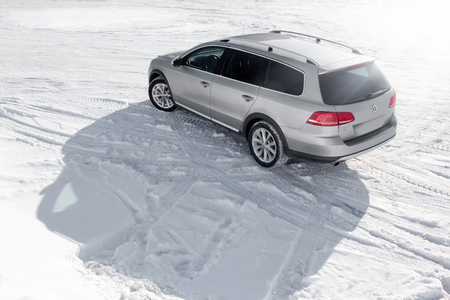 snow road: Saratov, Russia - January 26, 2014: Grey car Volkswagen Passat Alltrack stay on the snow road at winter daytime