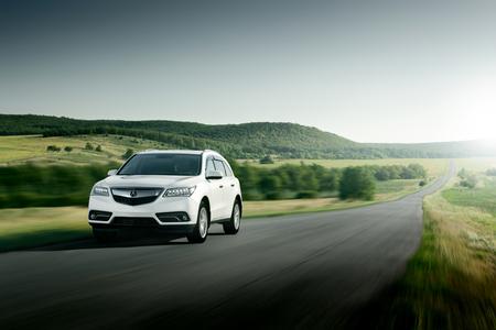 acura: Saratov, Russia - August 11, 2015: Modern car Acura MDX fast drive on asphalt road at sunset