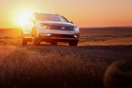 Saratov, Rusland - 2 juni 2014: De grijze Volkswagen Passat blijven op onverharde weg bij zonsondergang Redactioneel