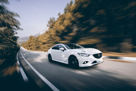 mazda: Crimea, Russia - September 20, 2015: White car Mazda speed driving on asphalt road at daytime