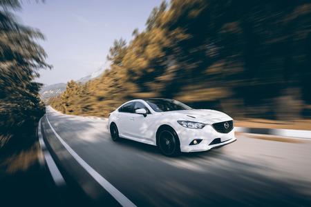 Crimea, Russia - September 20, 2015: White car Mazda speed driving on asphalt road at daytime