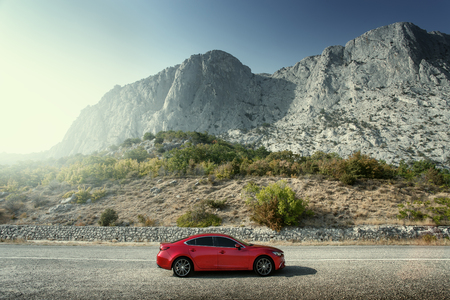 mazda: Crimea, Russia - September 20, 2015: Red car Mazda standing on the road near mountains at daytime Editorial