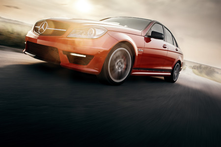 Saratov, Russia - August 24, 2014: Red Sport Car Mercedes-Benz C63 AMG Drive Speed On Asphalt Road At Sunset