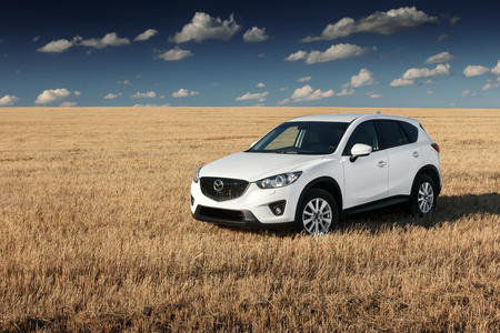 mazda: Saratov, Russia - August 30, 2014: White modern car Mazda CX-5 stay on yellow field at autumn