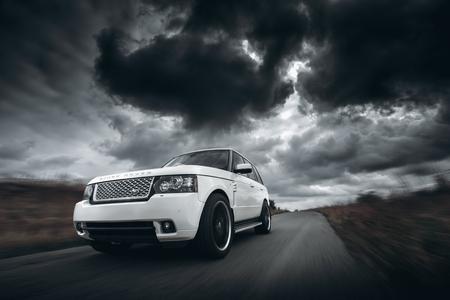 Saratov, Rusland - 11 oktober 2015: Witte auto Land Rover Range Rover snelheid rijden op de weg in dramatische wolken overdag