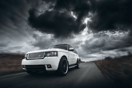 speed car: Saratov, Russia - October 11, 2015: White car Land Rover Range Rover speed driving on road at dramatic clouds daytime Editorial