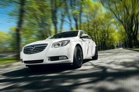 sedan: Moscow, Russia - May 07, 2015: White car Opel Insignia fast drive on asphalt road at daytime