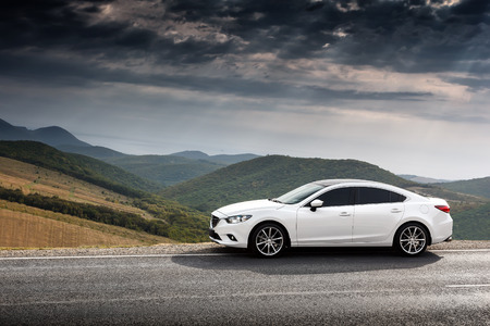 mazda: Krasnodar, Russia - September 07, 2014: White Car Mazda 6 parket at countryside asphalt road near green mountains at daytime