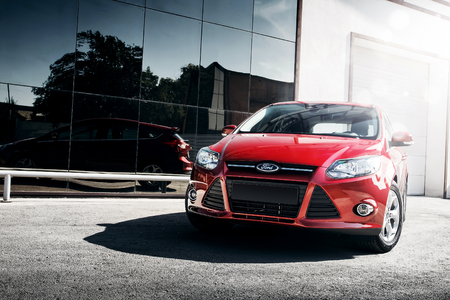 Engels, Russia - September 21, 2014: Red car Ford Focus III Sport standing near mirror build at daytime