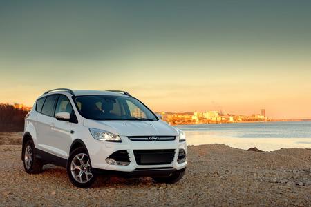 Saratov, Russia - November 25, 2014: White car Ford Kuga fast drive at stone coast at sunset Editöryel