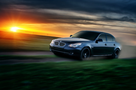 bmw: Saratov, Russia - April 30, 2013: Car BMW E60 drive at countryside road at sunset