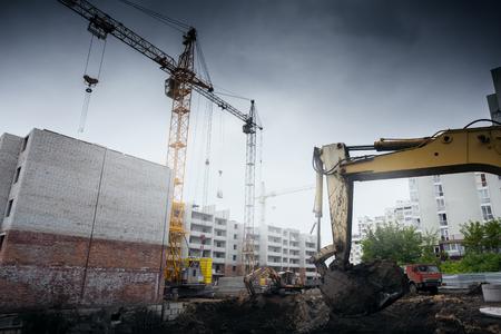 concrete commercial block: Crane construction bricks concrete building in city Stock Photo