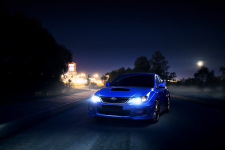 Moscow, Russia - June 18, 2016: Blue car Subaru Impreza WRX STI stay on asphalt countryside road near city and forest at moon night Editorial