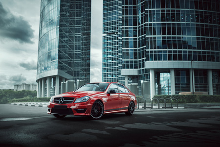 sportcar: Moscow, Russia - July 10, 2016: Red car Mercedes-Benz C63 AMG stay on asphalt road in the city Moscow at daytime