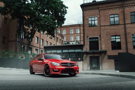 Moscú, Rusia - 10 de julio 2016: El coche rojo estancia de Mercedes-Benz C63 AMG en la carretera de asfalto en la ciudad de Moscú en el día Foto de archivo - 60669975