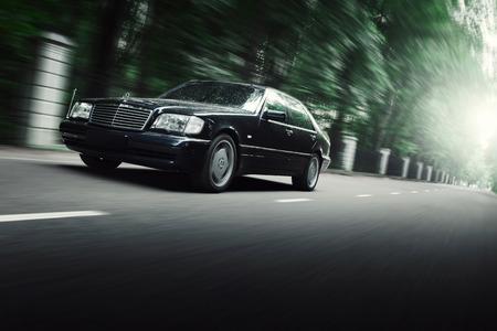 Mosca, Russia - 25 luglio 2016: Auto nera Mercedes-Benz Classe S W140 guidare su strada asfaltata nel parco naturale della città di Mosca al giorno Archivio Fotografico - 60669988