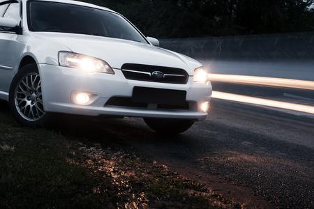 xenon: Saratov, Russia - August 28, 2014: Car Subaru Legacy stay on asphalt road near passing cars at dusk