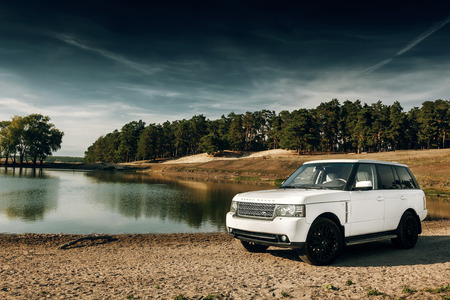 range of motion: Saratov, Russia - September 01, 2014: Car Land Rover Range Rover stand on sand near lake and forest at daytime