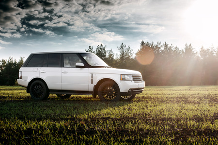Saratov, Russia - September 01, 2014: Car Land Rover Range Rover stand on green field near forest at sunset Editorial