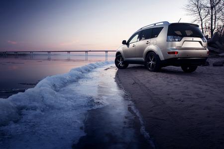 Saratov, Russia - November 27, 2014: Car Mitsubishi Outlander stay on ice coast at winter sunset Editorial