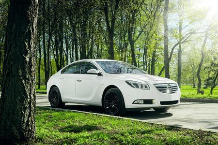 insignia: Moscú, Rusia - Mayo 07, 2015: Coche Opel Insignia surge sobre el asfalto en el bosque verde durante el día