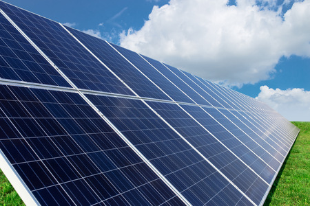 Solar panels generate power energy on blue sky at daytime Stock Photo
