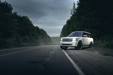 Saratov, Russia - August 08, 2016: Automobile bianca Land Rover Range Rover in piedi sulla strada asfaltata nei pressi della foresta al crepuscolo Archivio Fotografico - 62723513