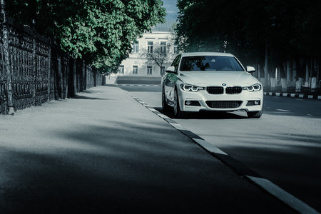 Saratov, Russia - May 07, 2017: White BMW 3 Series F30 car standing on empty asphalt road at summer daytime