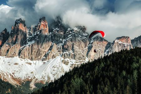 高い山の近くを飛行するパラグライダー。ドロミテ、イタリア
