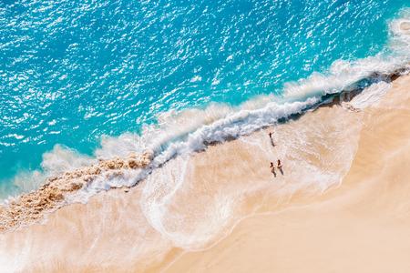 Vista aérea a la playa de arena tropical y al océano azul