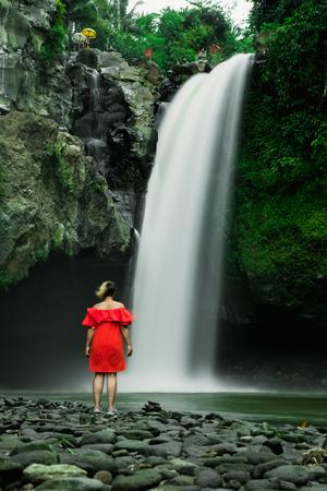 Woman in red dress is standing near big waterfall. Bali, Indonesia