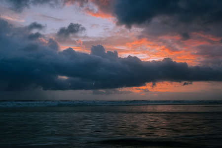 Dramatic golden sunset clouds reflected on the water sea. Tropical beach landscape at dusk