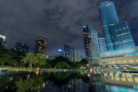 Business district downtown background, skyscrapers reflected in water. Kuala Lumpur City Centre Park at night