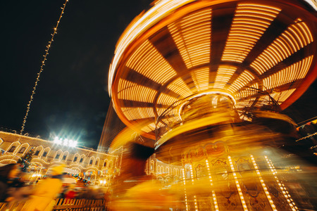 Carousel fast turning in motion illuminated at night  Banco de Imagens