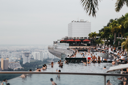 Singapore, Singapore - October 16, 2017: Viewpoint from infinity swimming pool of Marina Bay Sands hotel. Downtown landscape at golden sunset