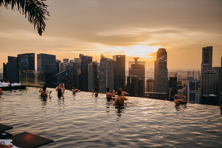 Singapore, Singapore - October 16, 2017: Business district aerial view from infinity swimming pool of Marina Bay Sands hotel. Downtown landscape at golden sunset Sajtókép