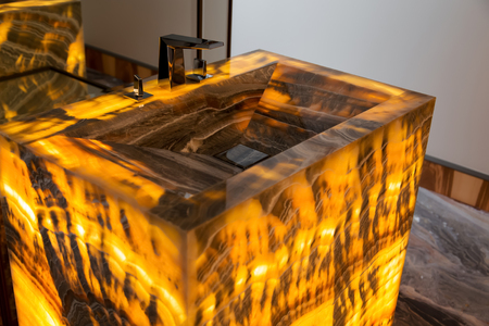 Illuminated glowing luxury marble sink and modern faucet in bathroom