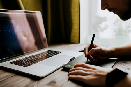 Man freelancer is working using laptop computer and graphics tablet at home office. Freelance lifestyle workplace