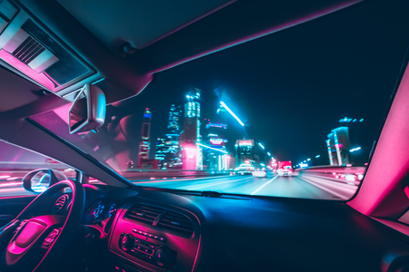 Car speed drive on the road in night city. Retro wave neon noir lights color toning 版權商用圖片