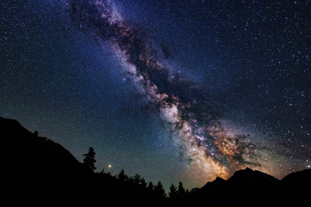 Astrophotography of Milky Way galaxy. Silhouette of mountains. Stars, nebula and stardust at night sky landscape 스톡 콘텐츠