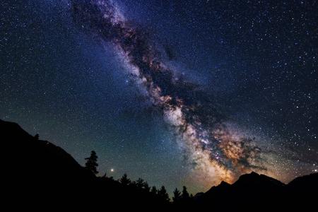 Astrophotographie de la galaxie de la Voie lactée. Silhouette de montagnes. Étoiles, nébuleuse et poussière d'étoiles au paysage de ciel nocturne Banque d'images