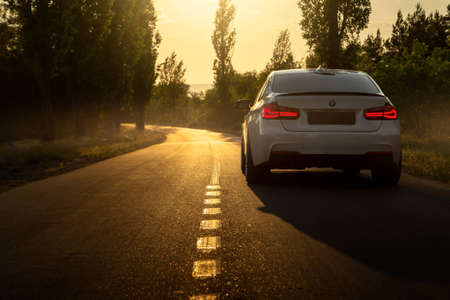 Engels, Russia - June 04, 2018: White car BMW 3 Series F30 is parked on empty countryside asphalt road at sunset Editorial