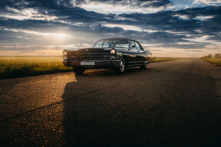 Engels, Russia - June 08, 2018: Black retro vintage muscle car Cadillac Fleetwood Brougham is parked at countryside asphalt road at golden sunset Editorial